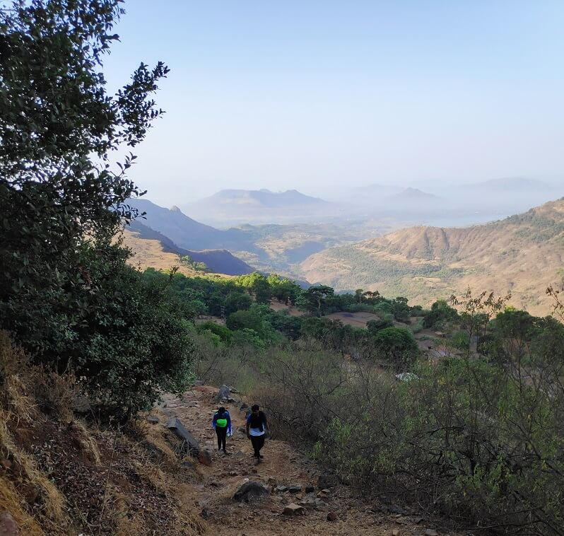 Two Trekkers passing through the tiny village in Matheran to reach Dasturi Naka