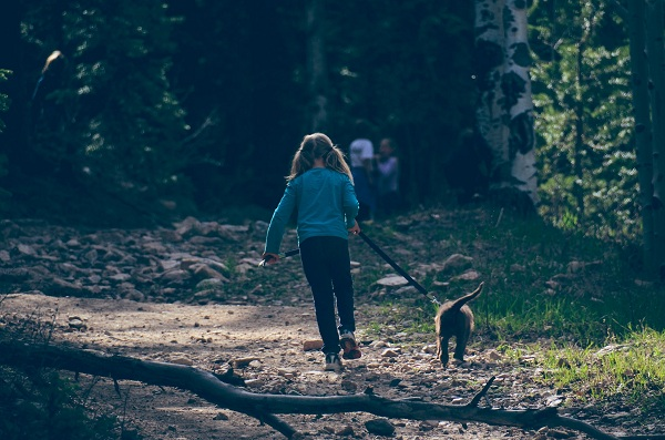 A little Girl Hiking in Jungle with leashed Dog
